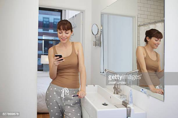 Woman text messaging in bathroom