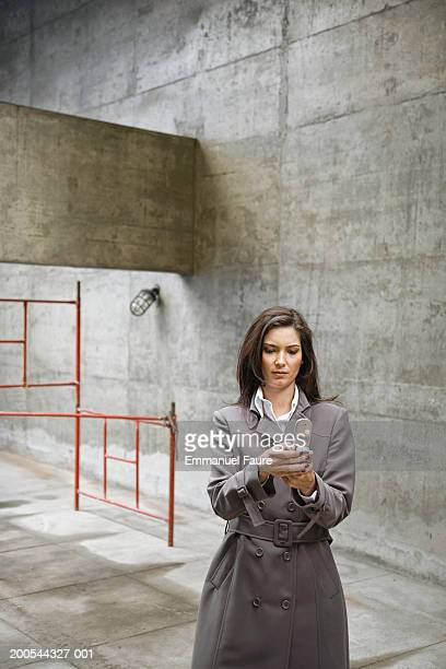 woman text messaging in concrete area, three quarter length - three quarter length ストックフォトと画像