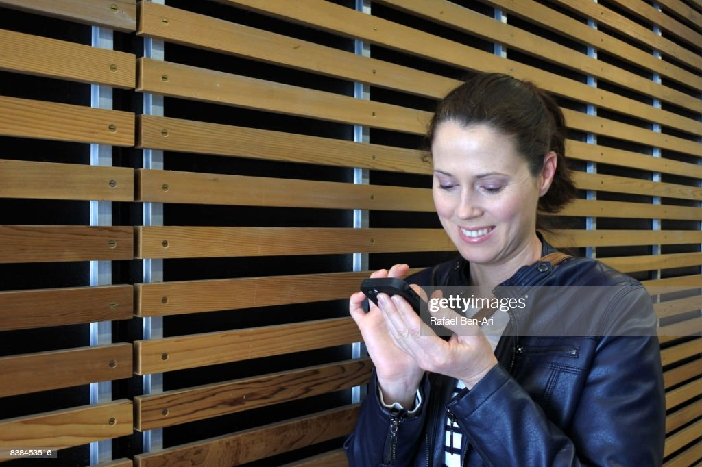 Woman text messaging on a mobile : Stock Photo