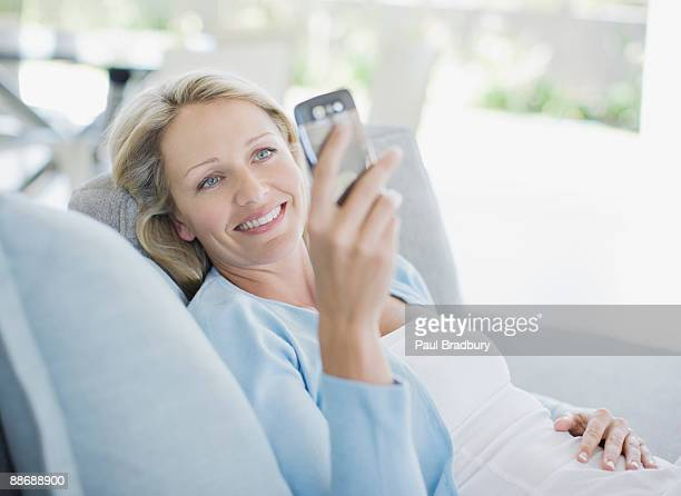 Woman text messaging on cell phone in living room