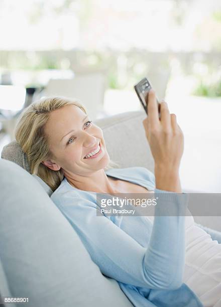 woman text messaging on cell phone in living room - mid adult women stock pictures, royalty-free photos & images