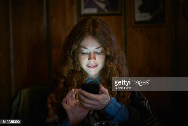 woman text messaging on her phone - sehen stock-fotos und bilder