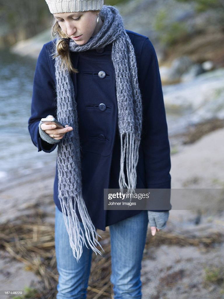 Woman text messaging outdoors : Stock Photo