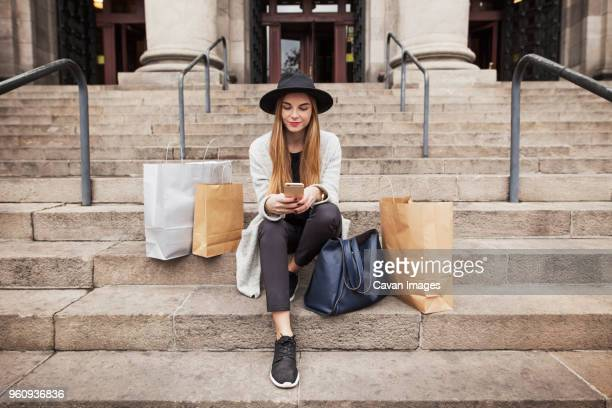 woman text messaging while sitting by shopping bags on steps - bag stock-fotos und bilder
