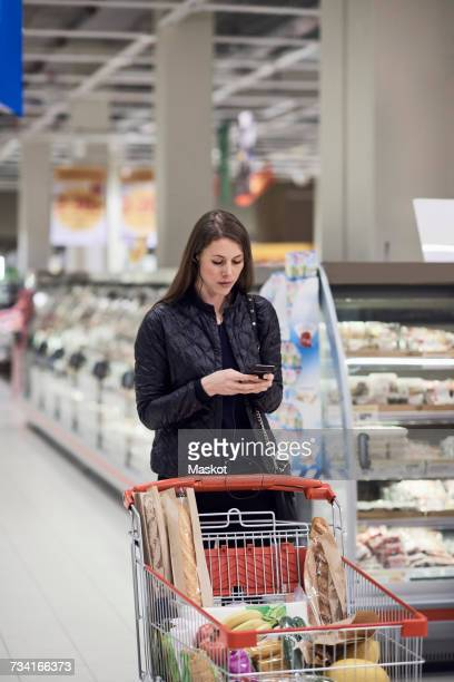 Woman text messaging while standing by shopping cart with groceries at supermarket
