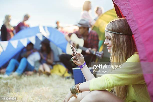 Frau SMS mit Handy im Zelt im music festival