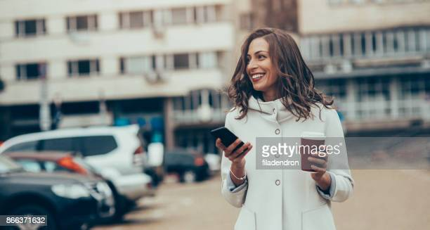 woman texting and drinking coffee in the city - parking lot stock pictures, royalty-free photos & images