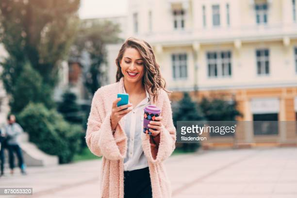 Woman texting and drinking coffee in the city