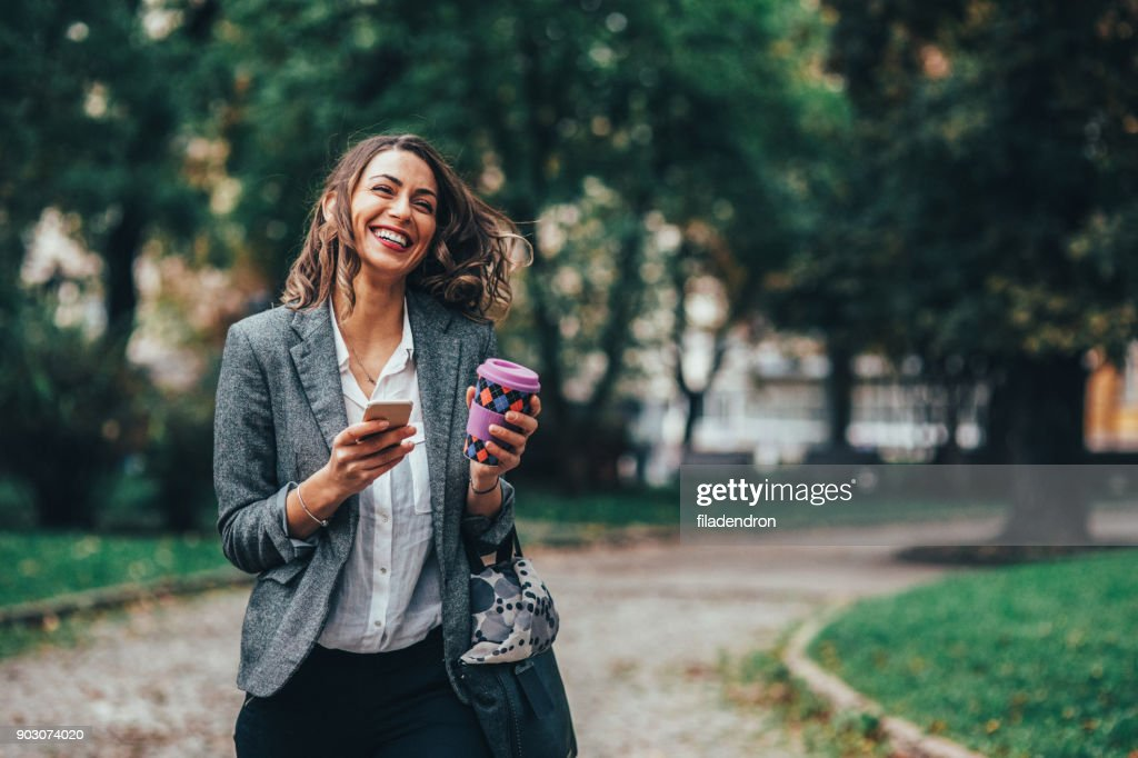 Mensajes de texto mujer y tomando café en el Parque : Foto de stock