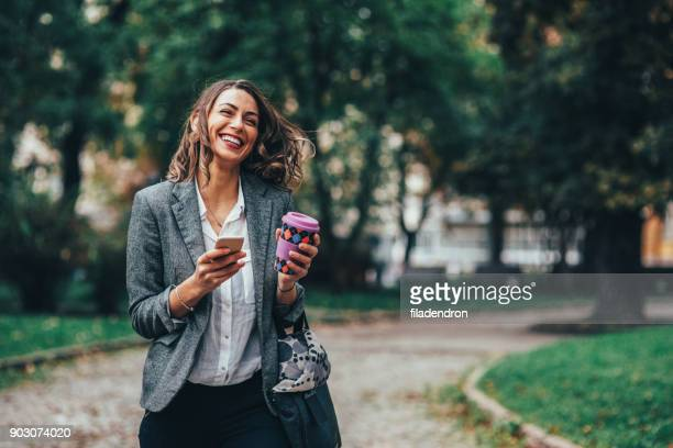 woman texting and drinking coffee in the park - public park stock photos and pictures