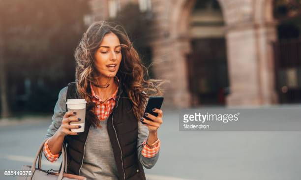 woman texting and drinking coffee outdoors. - istantanea foto e immagini stock