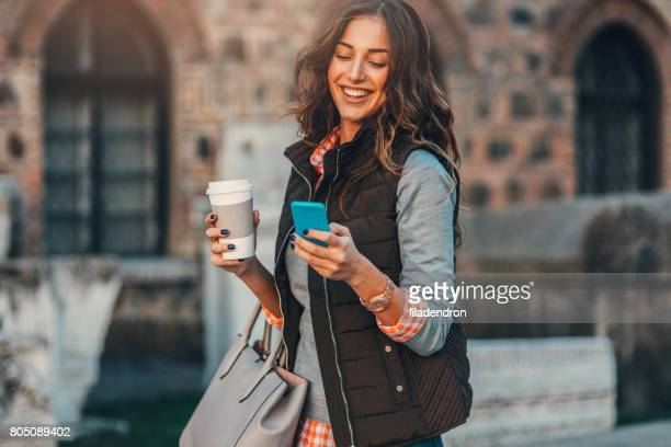 Woman texting and drinking coffee outdoors.