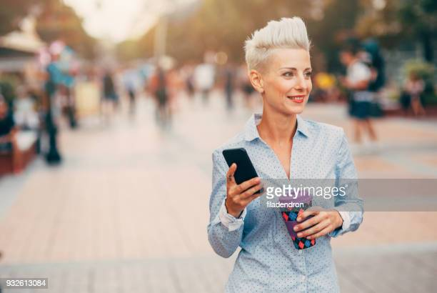 Woman texting and drinking coffee outdoors