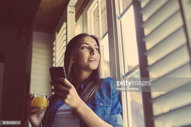 Woman texting and looking through the window