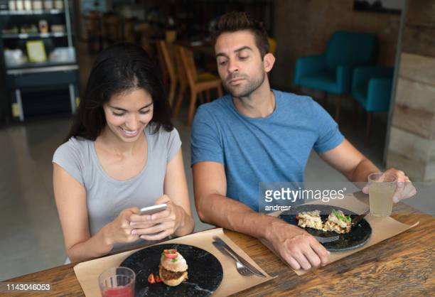 woman texting at a restaurant and boyfriend trying to see her phone - boyfriend stock pictures, royalty-free photos & images