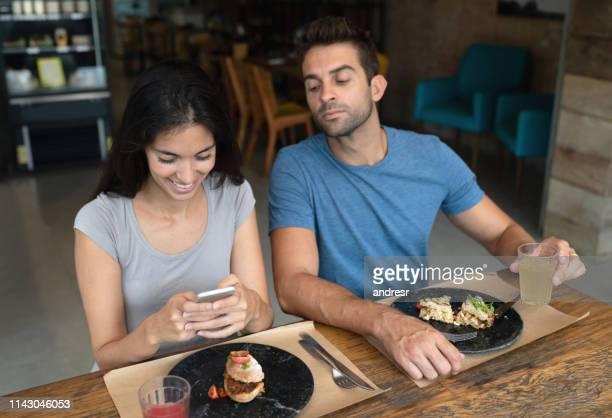 mulher que texting em um restaurante e em um noivo que tentam ver seu telefone - malícia - fotografias e filmes do acervo