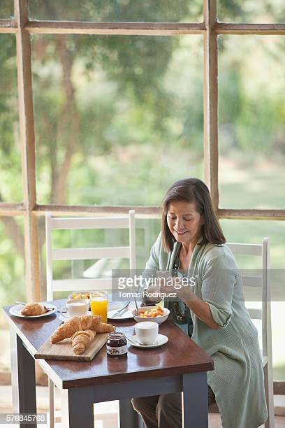 Woman texting at breakfast table
