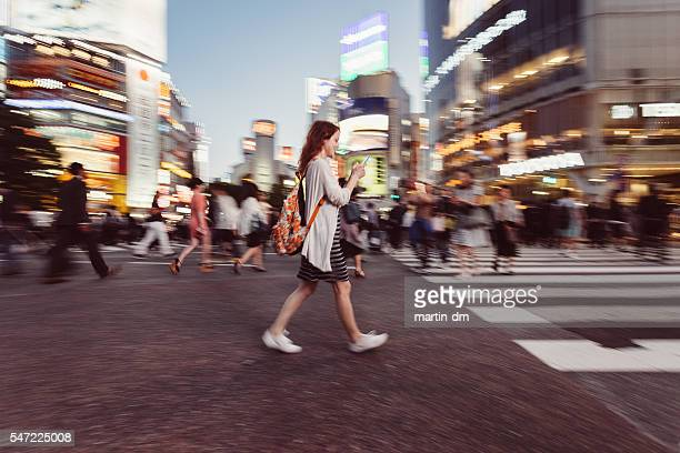 Woman texting at Shibuya crossing