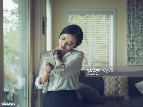 woman texting at window