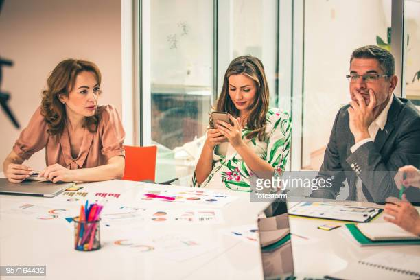 woman texting during business meeting - boredom stock pictures, royalty-free photos & images