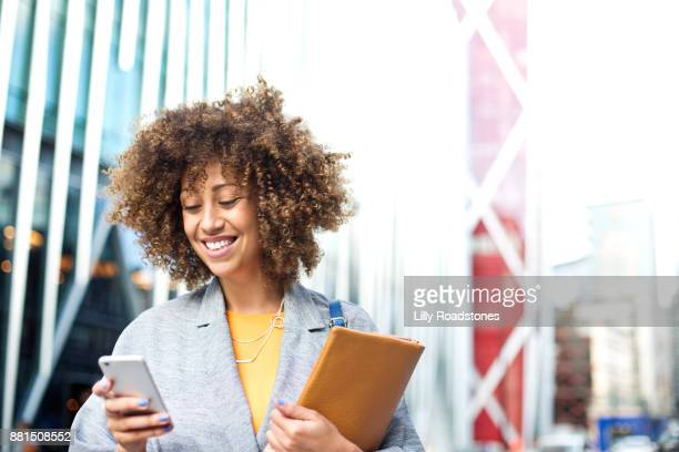 woman texting in city - afro amerikaanse etniciteit stockfoto's en -beelden