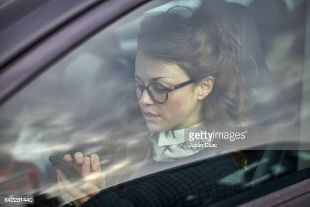 woman texting in her parked car viewed through the window