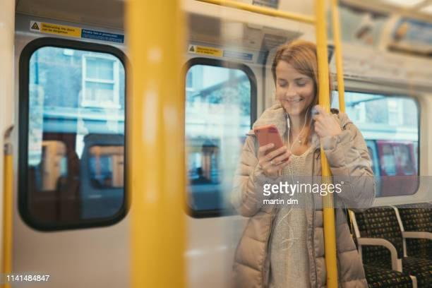 mujer enviando mensajes de texto en el autobús - vertical red tube fotografías e imágenes de stock