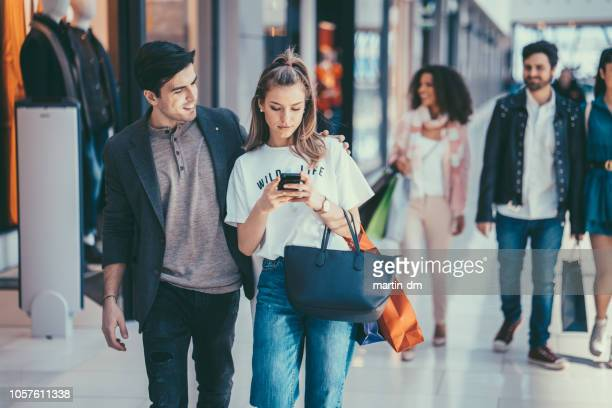 woman texting in the shopping mall and ignoring her boyfriend - ignore stock pictures, royalty-free photos & images