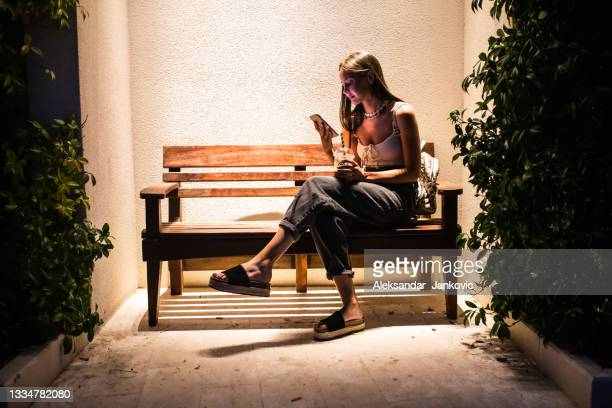 a woman texting on a bench - ambient light stock pictures, royalty-free photos & images