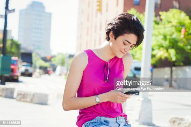 woman texting on cell phone in city street - hot pink stock photos and pictures