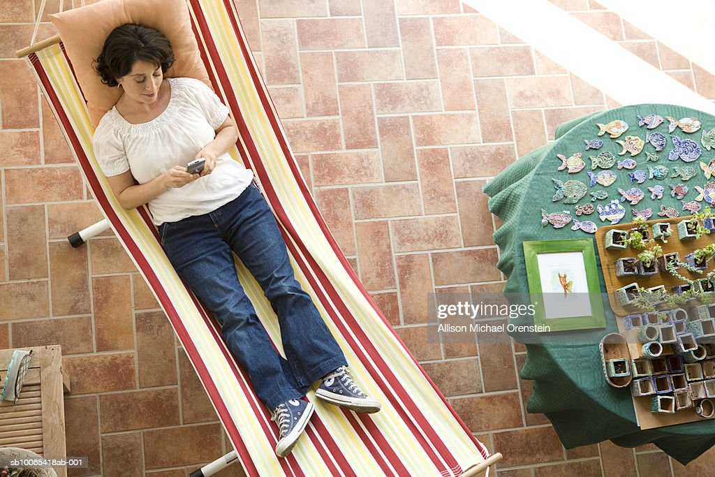 Woman texting on cell phone on hammock in house, elevated view : Foto stock