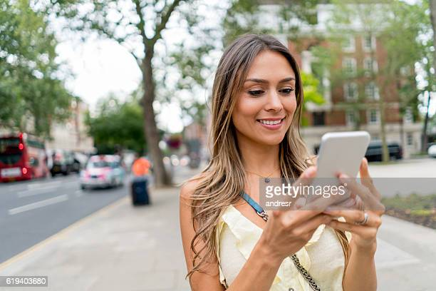 Woman texting on her cell phone outdoors