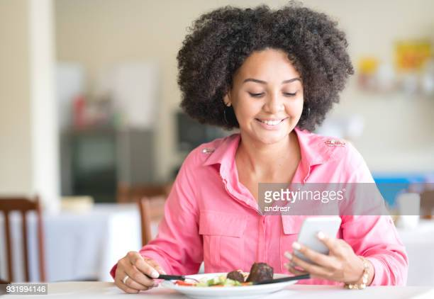 Woman texting on her cell phone while eating at a restaurant