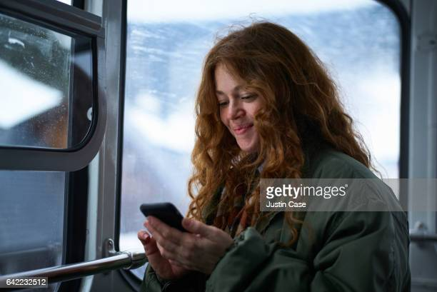 Woman texting on her phone in a subway in winter