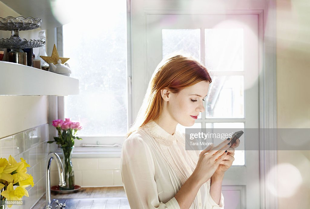 woman texting on mobile in kitchen : Stock Photo