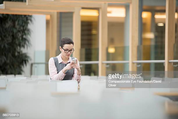woman texting on mobile phone in cafe - cef do not delete stock pictures, royalty-free photos & images