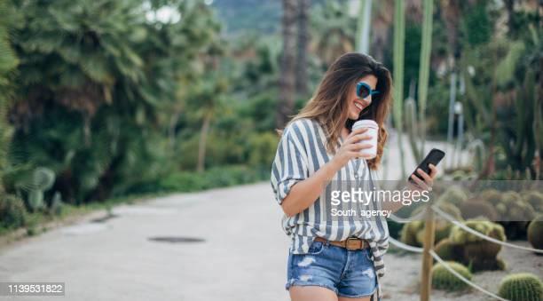 mujer enviando mensajes de texto en el teléfono en el parque público - pantalón corto fotografías e imágenes de stock
