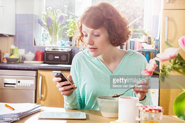 Woman texting on phone while eating breakfast.