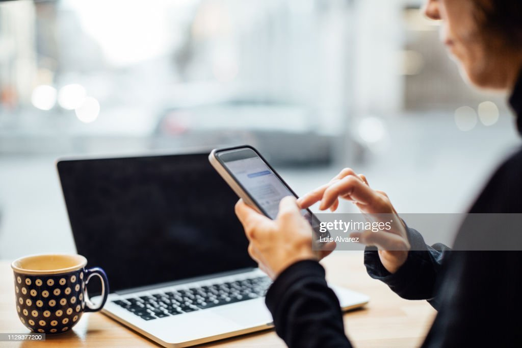 Woman texting on smart phone at cafe : Stock Photo