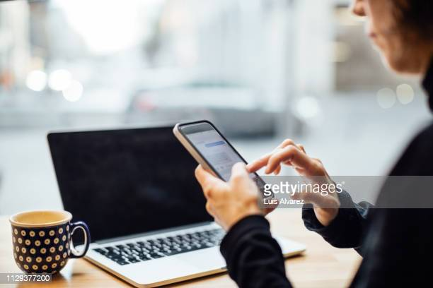 woman texting on smart phone at cafe - social media stockfoto's en -beelden