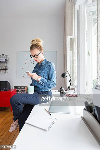 Woman texting on smart phone in an office