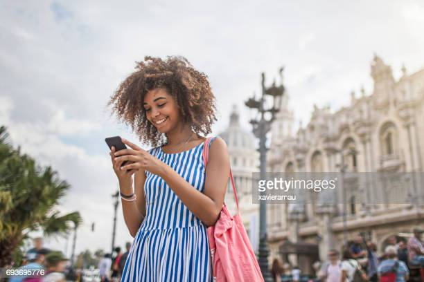 Woman texting on smart phone in city