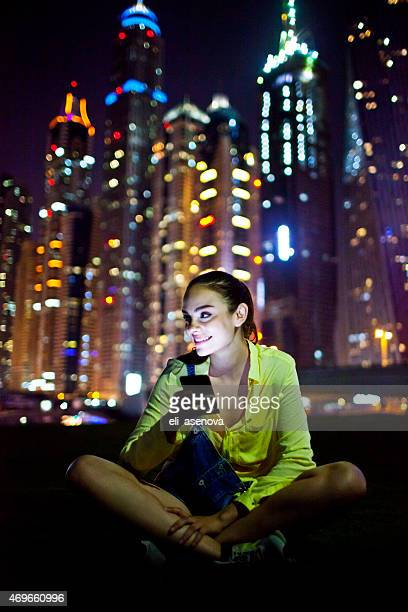 Woman texting on the smart phone in Dubai Marina