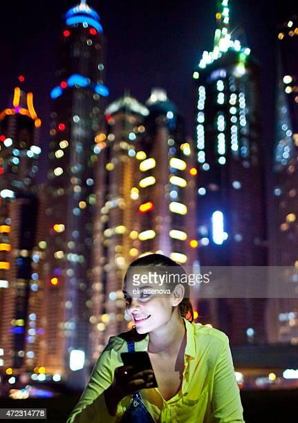Woman texting on the smart phone in Dubai Marina.