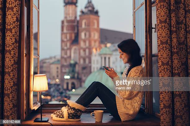 woman texting on the window sill - poland stock pictures, royalty-free photos & images