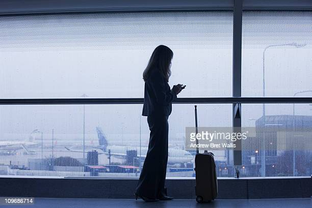 Woman texting overlooking an airport runway