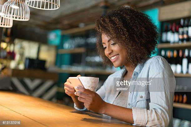 Woman texting while having a cup of coffee