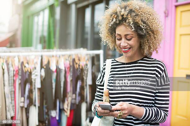 Woman texting while shopping at street market