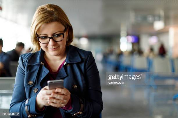 Woman texting while waiting for a flight at airport