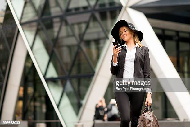 woman texting while walking, 30 st mary axe in background, london, uk - ben diamond stock pictures, royalty-free photos & images